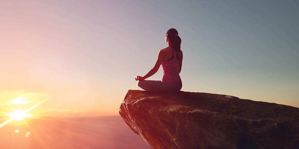 Woman practices yoga and meditates on the mountain.